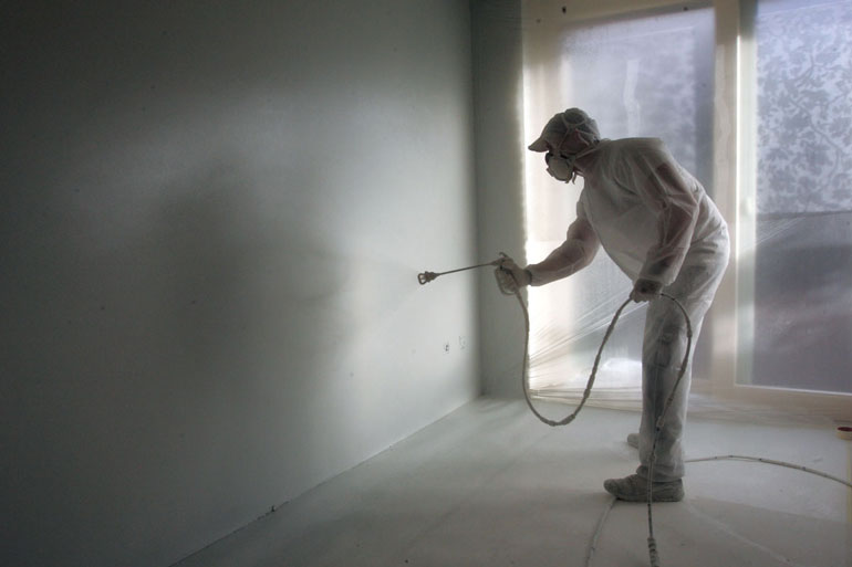 een muur met behang laten overspuiten met latex muurverf